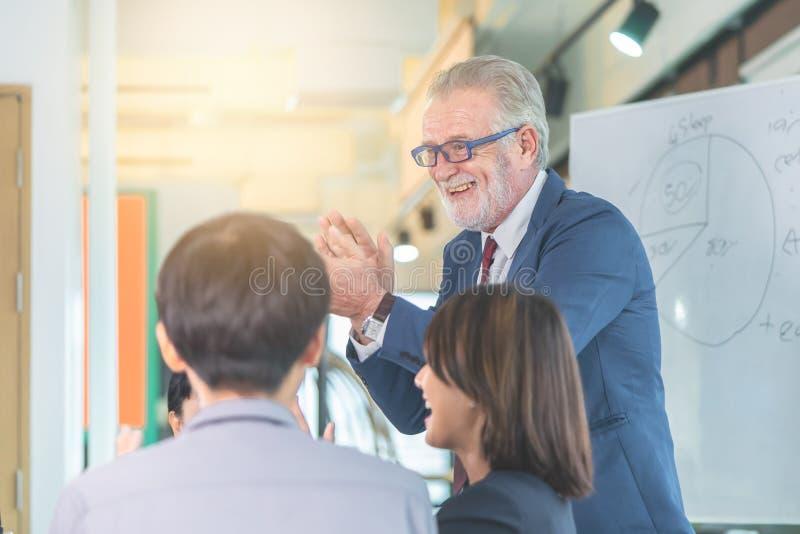 资深上司在办公室会议祝贺队企业成功的 免版税图库摄影