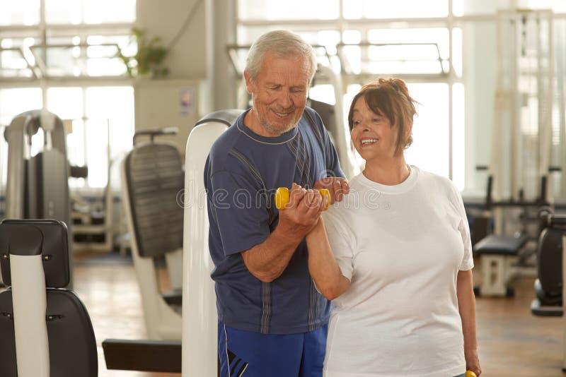资深与她的丈夫的妇女举的重量 图库摄影