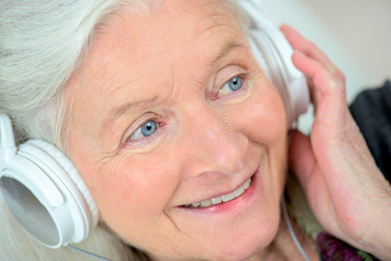 资深与耳机的妇女听的音乐 库存图片