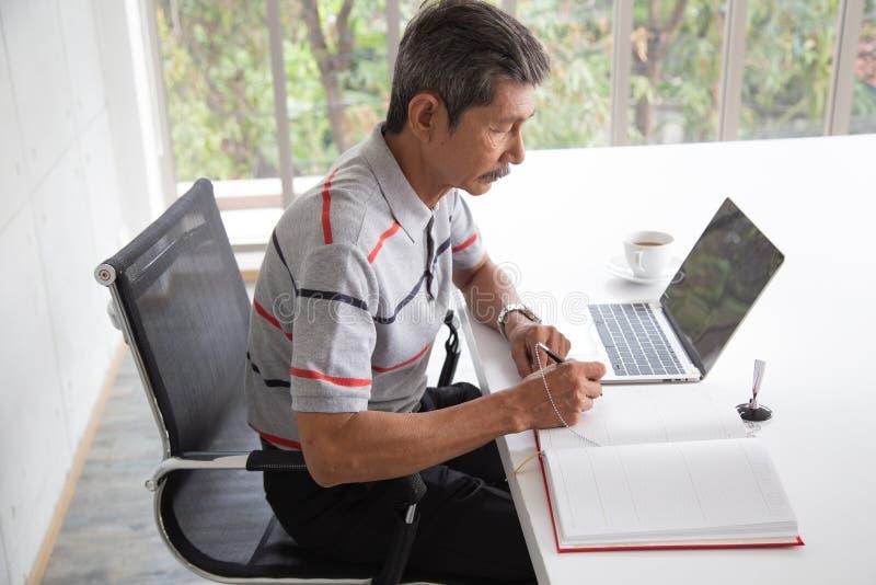 资深亚洲商人微笑和签到合同文件 库存照片
