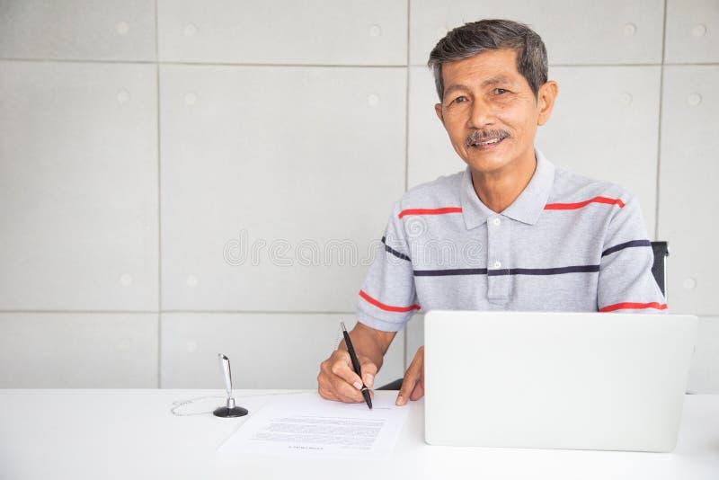 资深亚洲商人微笑和签到合同文件 免版税图库摄影
