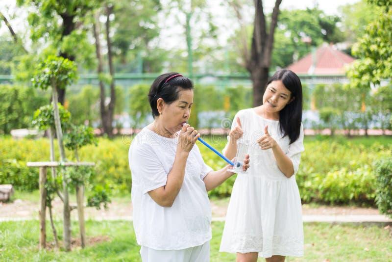 资深亚洲母亲打击刺激性肺量计或三个球为刺激肺,鼓励女儿小心和支持 免版税库存图片