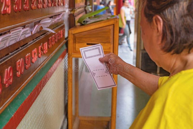 资深亚裔妇女在曼谷拾起在龙莲寺寺庙的中国每日算命先生一定报纸 免版税库存照片