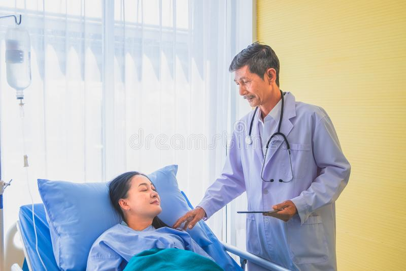 资深亚裔男性医生参观和谈话与病区的中年女性患者 免版税库存图片