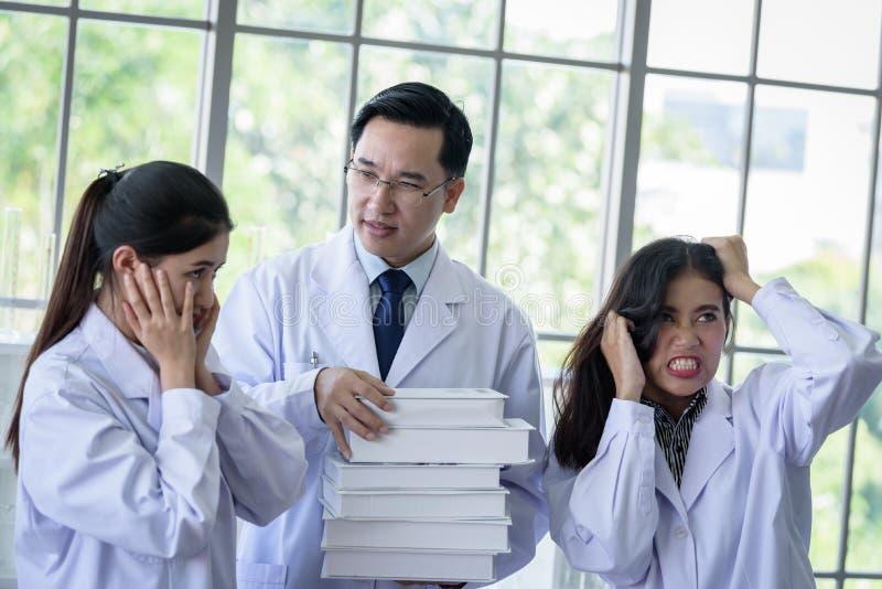 资深亚裔科学家有分配新的工作到学生在实验室 库存图片
