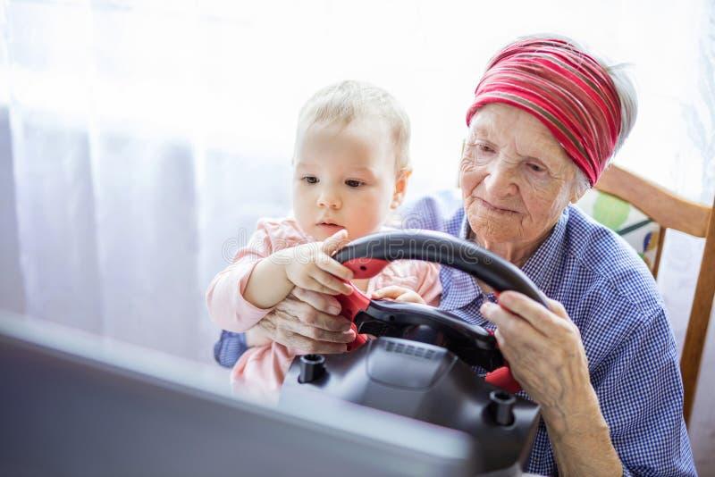 资深享受在膝上型计算机的妇女和她的重孙女小汽车赛电子游戏 图库摄影