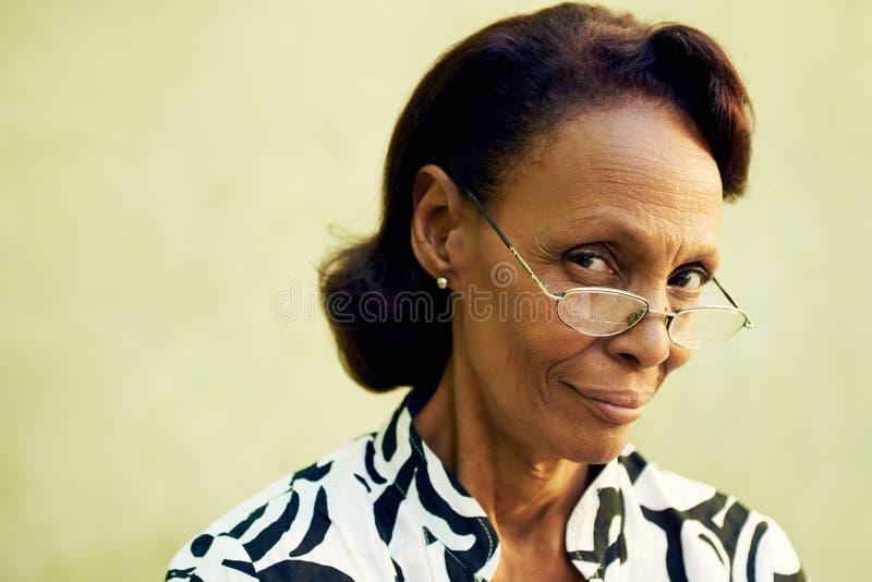 确信的老黑人夫人画象有镜片微笑的 免版税库存图片