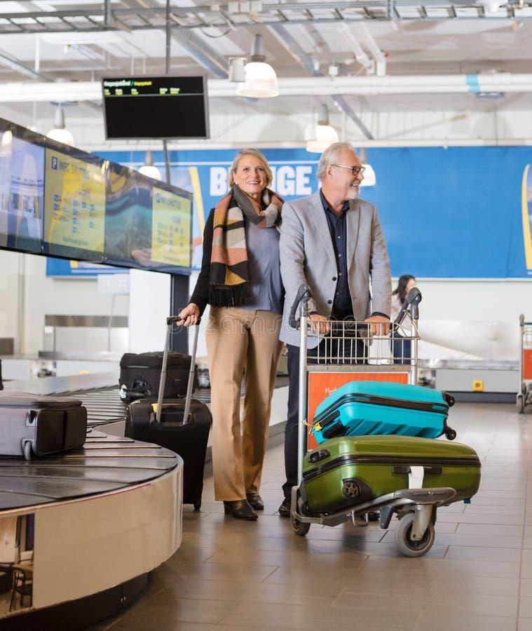 资深企业加上在推车的行李在机场 免版税库存图片