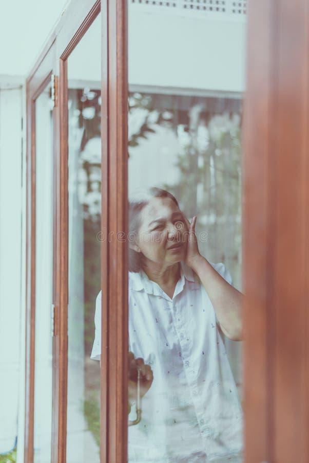 资深健康概念,成熟亚裔年长妇女有偏头痛和头疼痛苦在窗口附近在家 免版税库存照片