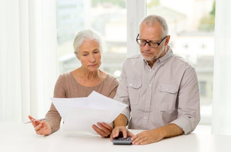 资深加上纸和计算器在家 免版税库存照片