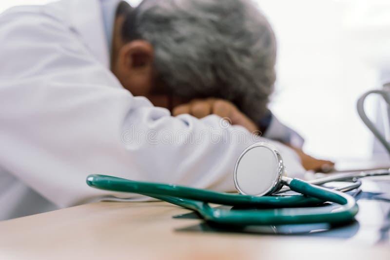 资深医生在他的甲板劳累过度疲倦和睡觉在医疗办公室 库存照片