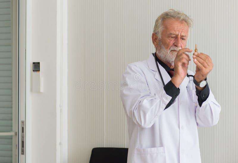 资深医生男性在医院准备给与射入的疫苗或注射器害怕的患者 免版税图库摄影