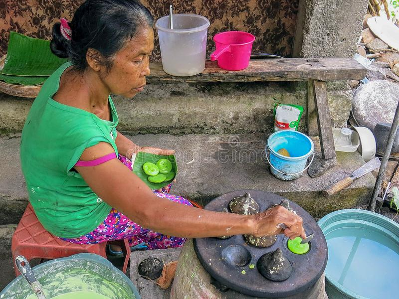 资深印度尼西亚妇女准备传统甜盘 由被烘烤以石形式的面团做的一个非常鲜美点心 Primiti 图库摄影