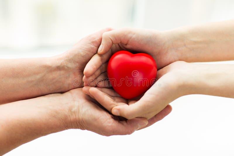 资深和少妇递拿着红色心脏 免版税库存图片