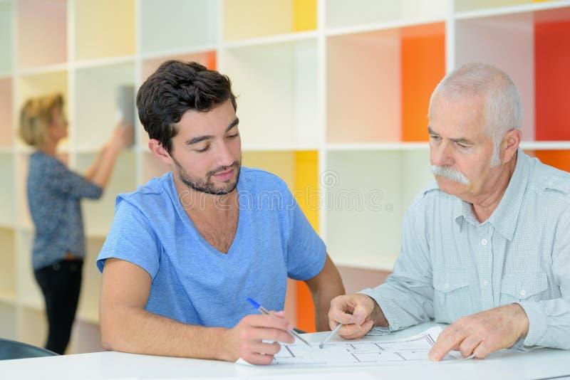 资深和年轻商人一起谈论在桌上 免版税库存图片