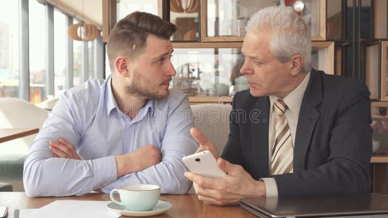 资深商人显示他的伙伴某事在他的智能手机 免版税图库摄影