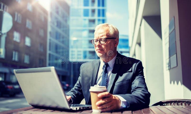 资深商人用膝上型计算机饮用的咖啡 免版税库存照片