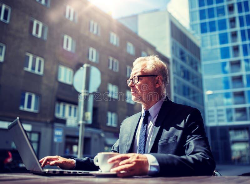 资深商人用膝上型计算机饮用的咖啡 库存图片