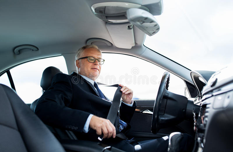 资深商人紧固汽车座位传送带 免版税库存图片