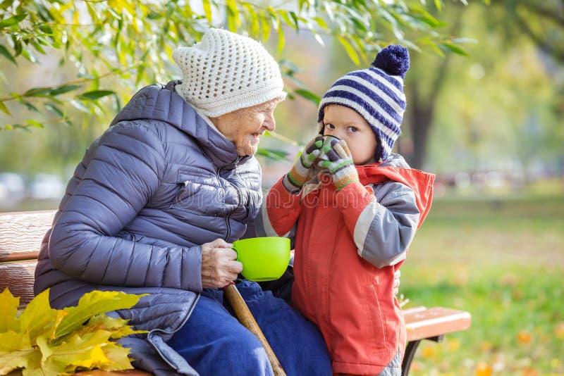 资深喝热的茶的妇女和她的重孙子 免版税库存照片