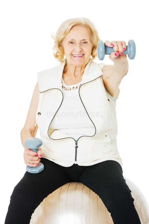 资深在健身球的妇女举的哑铃 库存照片