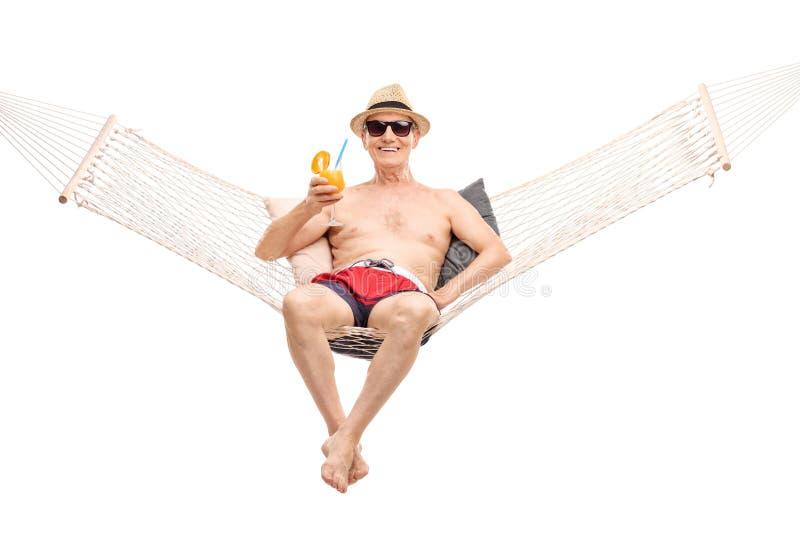 资深在吊床和喝鸡尾酒 免版税库存图片