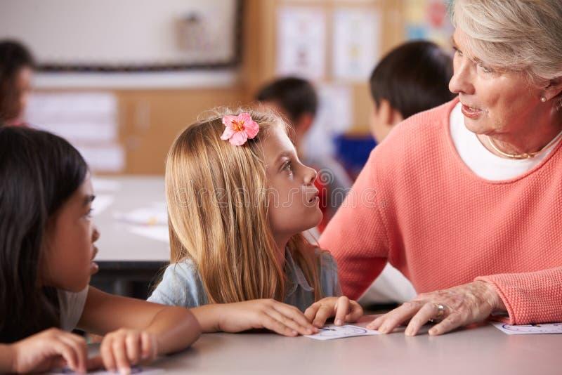 资深在小学教训的老师帮助的学生 免版税库存照片