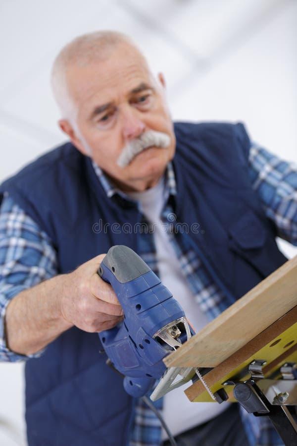 资深在木板条的木匠钻孔在车间 库存图片