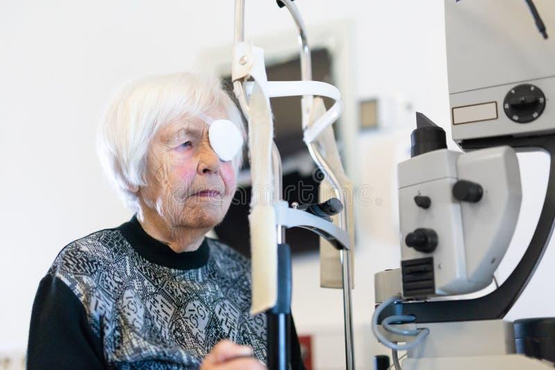 资深在激光手术做法以后的妇女佩带的眼睛pathc在眼科学诊所 库存图片