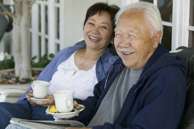 资深在门廊微笑的夫妇饮用的茶 图库摄影