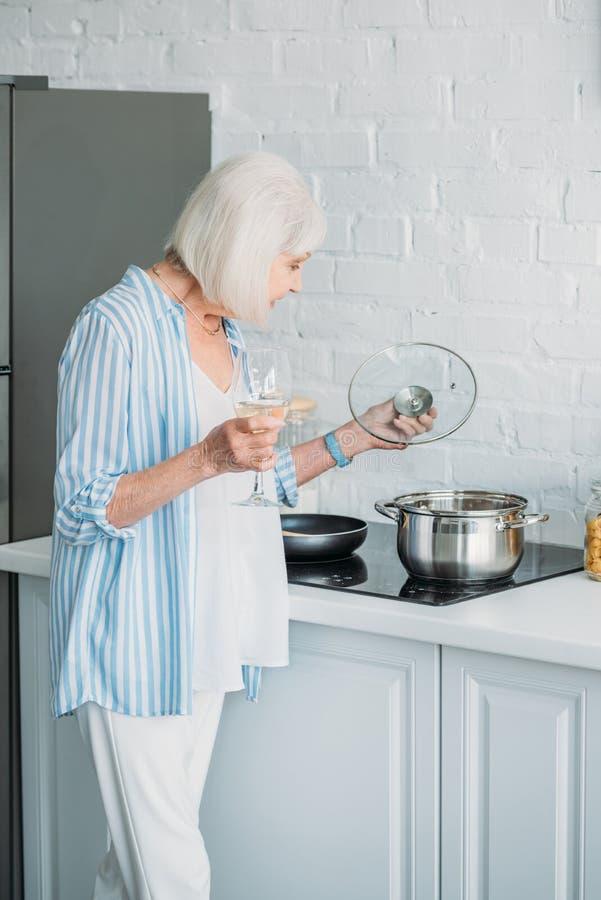 资深夫人侧视图有酒检查在火炉的杯的平底深锅 库存图片