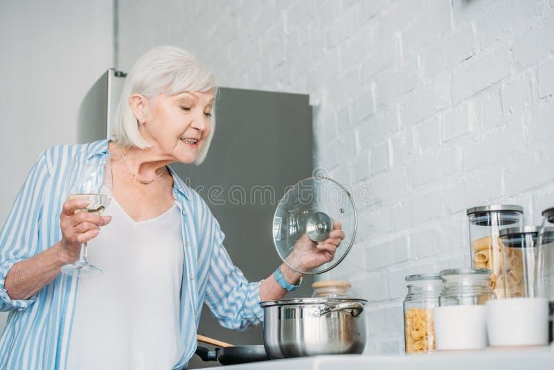 资深夫人侧视图有酒检查在火炉的杯的平底深锅 库存照片