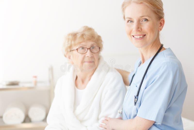 资深夫人在有护士的家 免版税库存图片