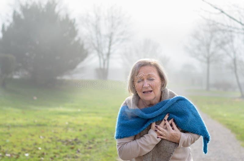 资深夫人在痛苦中的抓住她的胸口 图库摄影