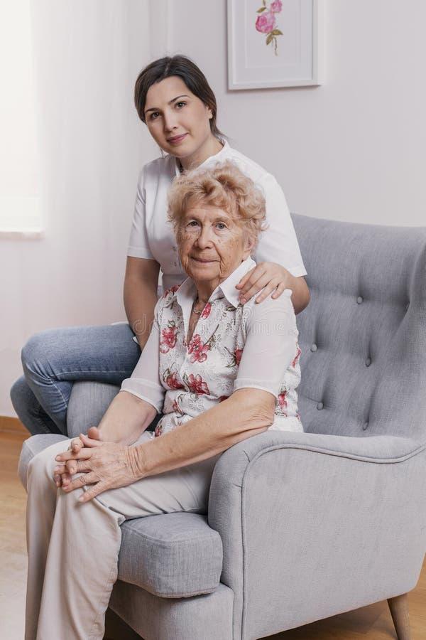 资深夫人坐在扶手椅子的在老人院,在她后的支持的护士 免版税库存照片