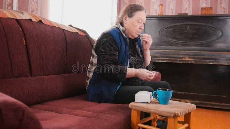 资深夫人-年长妇女在家采取药片疗程包裹-退休金医疗保健 免版税库存照片