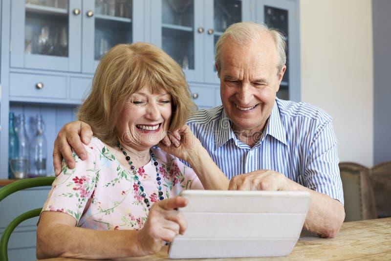 资深夫妇一起在家坐使用数字式片剂 免版税库存图片