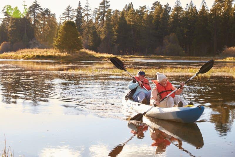 资深夫妇划皮船在湖的,正面图 库存照片