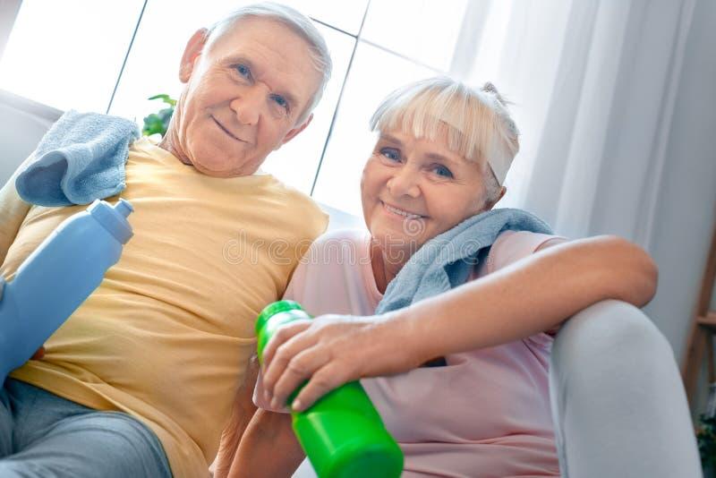 资深夫妇在家一起行使医疗保健饮用水 库存图片