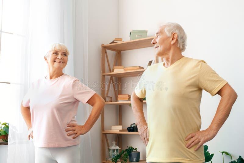 资深夫妇在家一起行使在看在彼此的腰部的医疗保健手 免版税库存照片
