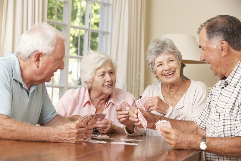 资深夫妇在家享受卡片的比赛小组 免版税库存图片
