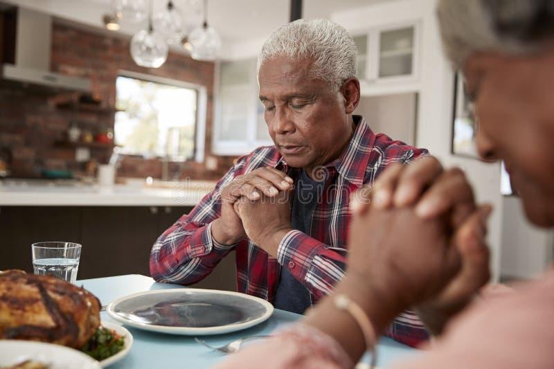 资深夫妇在家说雍容在膳食前在表附近 免版税库存图片