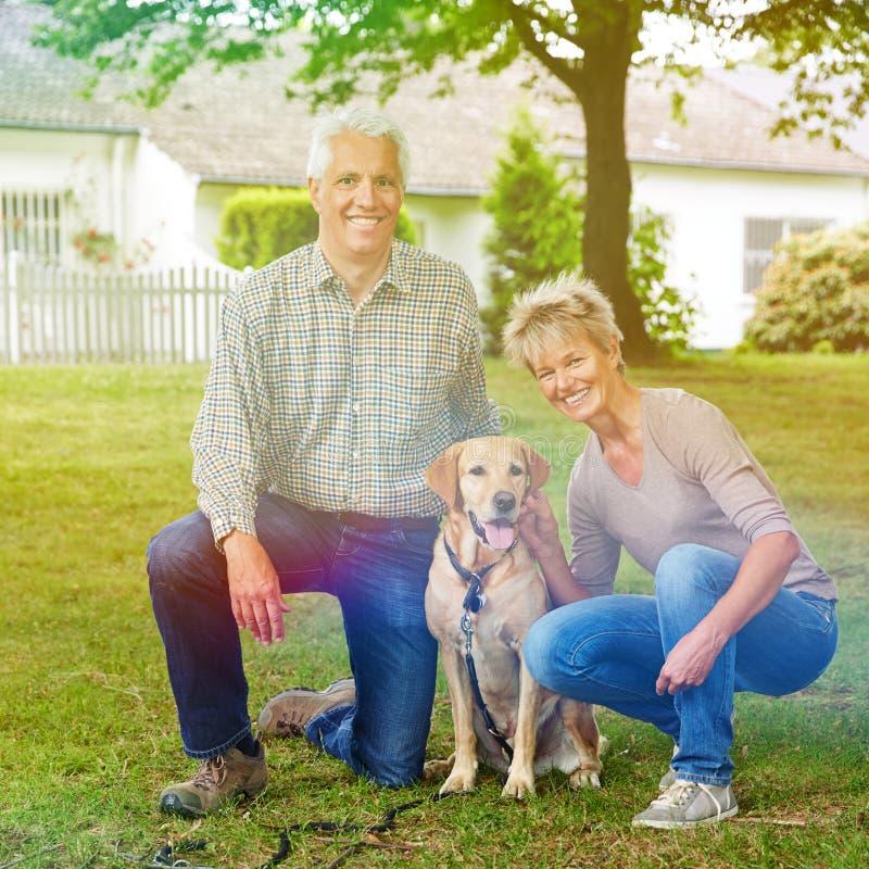 资深夫妇在有狗的庭院里 免版税图库摄影