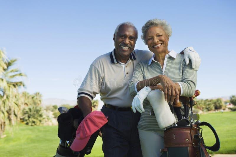资深夫妇在高尔夫球场 图库摄影