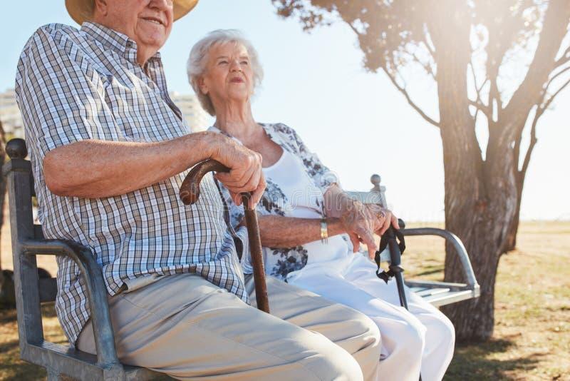 资深夫妇坐一条长凳用拐棍 库存照片