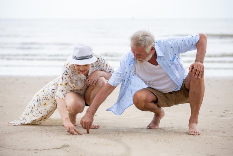 资深夫妇坐使在沙子的海滩心脏一致,妇女亚裔人白种人 库存图片