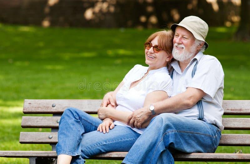 资深夫妇坐公园长椅 免版税图库摄影
