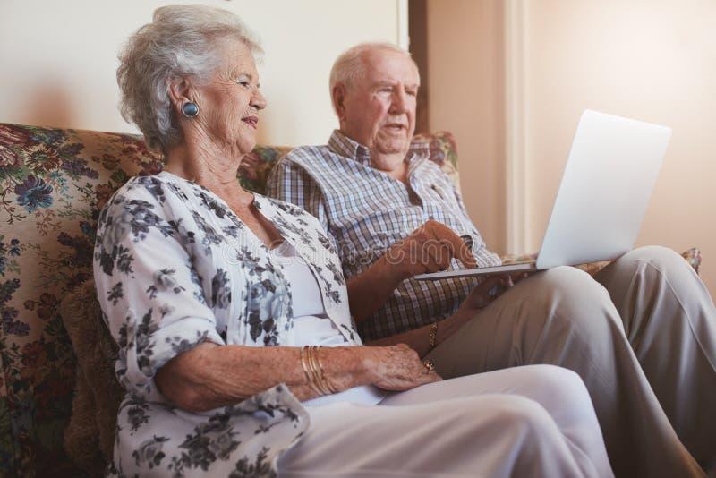 资深夫妇坐有膝上型计算机的一个长沙发 免版税库存照片