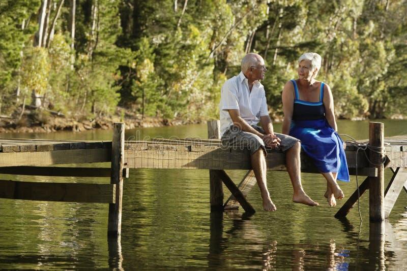 资深夫妇坐码头在湖 库存图片