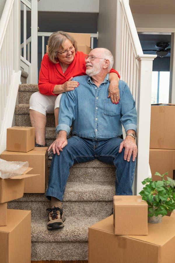 资深夫妇坐移动围拢的台阶箱子 免版税图库摄影
